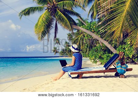 remote work cocept -young woman with laptop on tropical beach vacation