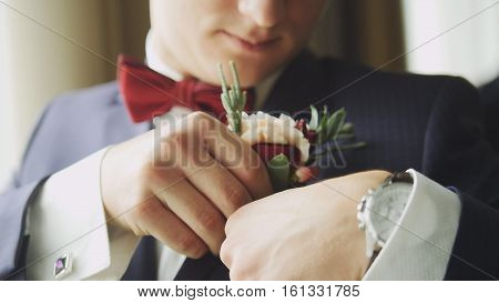 Fashion young man in bow tie and clock - groom's hand arranging boutonniere flower on suit, close up