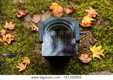 Lense with holder and graduated ND filter with autumn foliage on the yard. This filter uses for landscape photography.