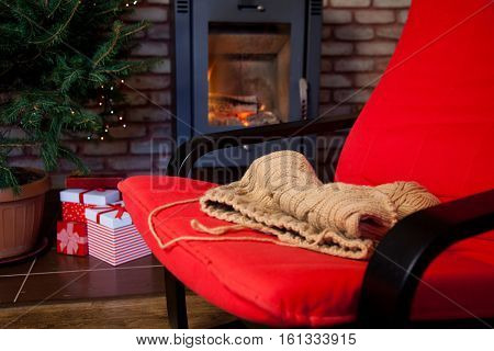 woolen knitwear on red armchair- burning fireplace and Christmas tree with presents in the backgroung- cozy home concept