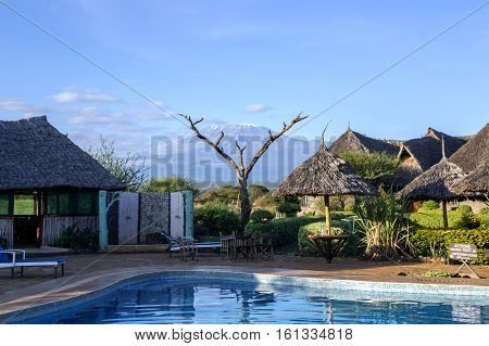 AFRICA, TANZANIA, MAY, 10, 2016 - Swimming pool with views of the mountain Kilimanjaro without clouds with a small cap of snow in Amboseli National Park, Tanzania