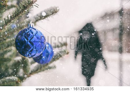Woman walking on a sidewalk in Montreal during a snowstorm in winter with Christmas blue balls in the foreground