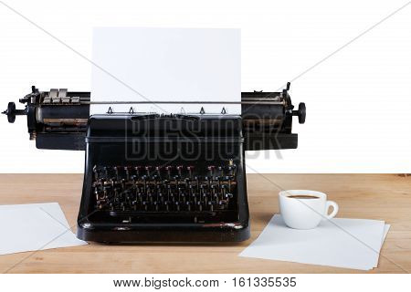 Vintage typewriter with paper sheet on wooden table with coffee cup, isolated on white background. Old writing equipment. Press, blogging and journalism concept.