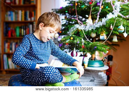 Beautiful little school kid boy reading a book near Christmas tree with lights and illumination. Happy child in pajama sleepwear having fun with book gift. Celebrating family holiday. Education
