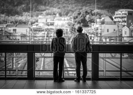 KYOTO, JAPAN - NOVEMBER 11, 2016: People waiting for train on the train station in Kyoto, Japan. West Japan Railway (JR West) is one of the biggest railway companies in Japan.
