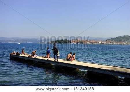 SLOVENIA PIRAN - SEPTEMBER 1: People sunbathing on a pontoon at the Adriatic Sea on September 1 2016 in Piran.