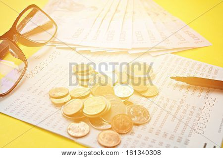 Business, finance, investment or savings concept : Savings account passbook, Thai money, coins, eye glasses and pen on yellow background
