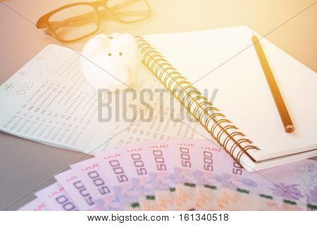 Business, finance, investment or savings money background concept : Blank notebook, pencil, savings account passbook, eye glasses, Thai money and piggy bank on gray background