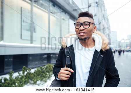 Photo of a handsome african young man walking on the street. Looking aside.
