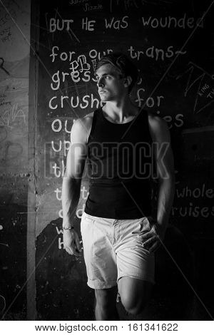 Close Up Image Of A Good Looking Male Model In A Subway With Grafitti Against The Walls, Wearing A V