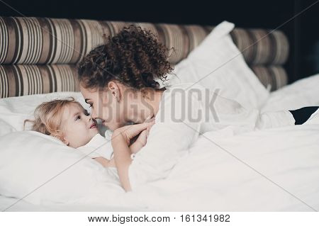 Smiling woman lying in bed with her baby girl 2-3 year old in hotel. Looking at each other. Motherhood. Childhood.