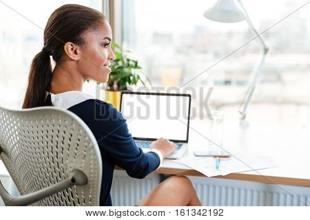 Back view of african business woman in dress sitting by the table near the window in office with laptop and looking aside