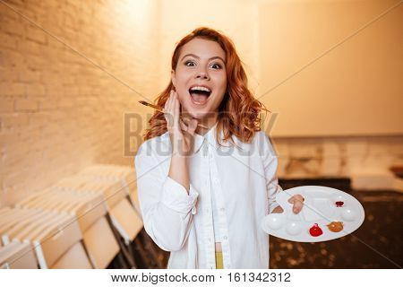 Photo of shocked happy young redhead woman painter with oil paints and palette. Look at camera.
