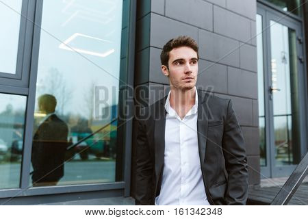 Serious business man in suit standing near the office building and looking aside