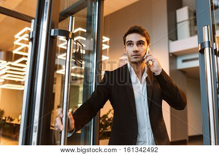 From below image of Serious business man in suit talking on phone in office and holding the door