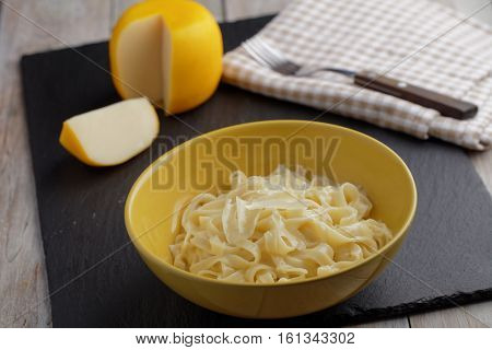 Fettuccine Alfredo with Parmesan cheese on a rustic table