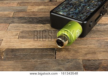 Rostov - on - Don, Russia - December 12, 2016: Modern electronic mech mod vaping device. Electronic cigarette on a wooden background.