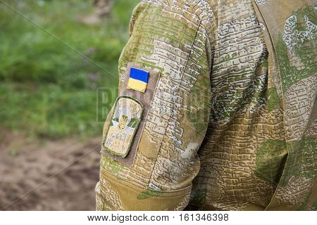 PABRADE / LITHUANIA - AUGUST 8 2016: Ukraine national flag with an army patch on a military field jacket