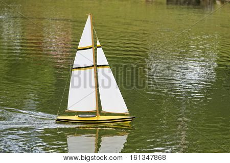 Remote Sailboat Gliding Through The Green Water