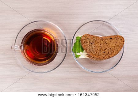 Bread with cheese and parsley and hot tea in a cup on the table.