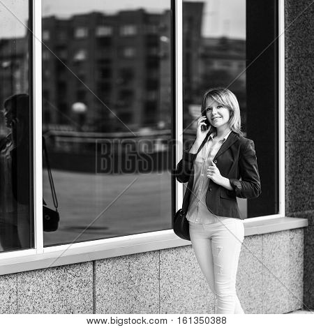 Young businesswoman speaking on the phone while standing near building