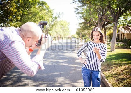 Close up image of a photographer taking pictures of a model for stock photography