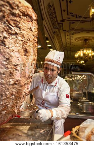 ISTANBUL TURKEY - OCTOBER 6 2014: A chef cutting traditional Turkish food Doner Kebab in a street food shop