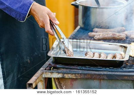 Preparing tradition south african boerewors / sausage on a braai / grill / barbeque