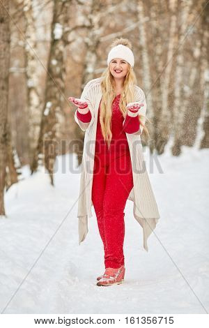 Young smiling woman stands in snowy winter park with handfuls of snow in hands.