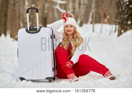 Young smiling woman sits near trolley bag, propping head with hand in winter park.