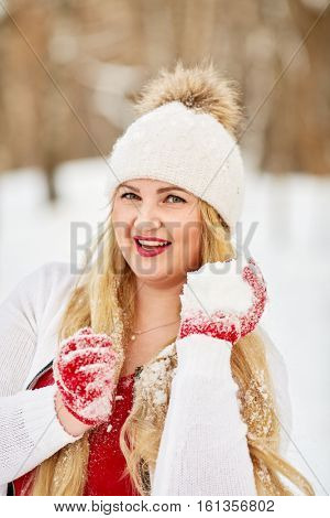 Portrait of young smiling woman holding handful of snow in hand.