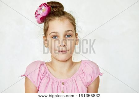 Portrait of girl in pink blouse and flower in heardo.