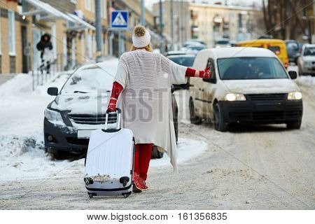 Young woman with trolley bag tries to catch cat on snow-covered road, rear view.