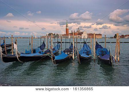 gondolas moored on the Grand Canal in Venice on the background basilica San Giorgio Maggiore, Italy