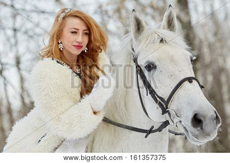 Young woman in white dress and white fur mantle strokes white horse in park.