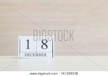 Closeup surface white wooden calendar with black 18 december word on blurred brown wood desk and wood wall textured background with copy space selective focus at the calendar