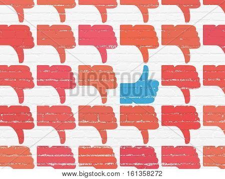 Social media concept: rows of Painted red thumb down icons around blue thumb up icon on White Brick wall background