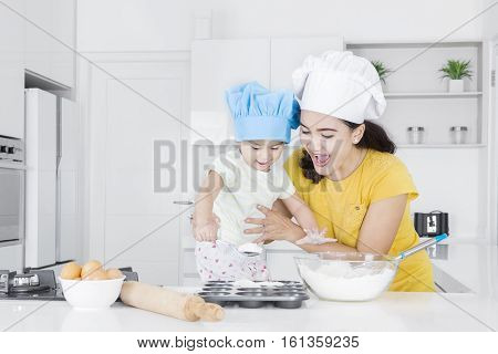 Portrait of happy mother and cute daughter making bakery with flour in the kitchen