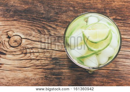 refreshing lemonade with green lemon and ice close-up view from above toning photo
