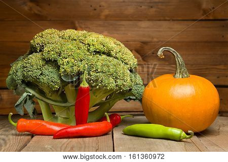 Fresh healthy useful vegetables broccoli, pumpkin, peppers on wooden table close up.