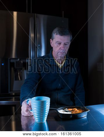 Lonely and depressed senior male sitting alone at kitchen table eating a microwaved ready meal of curry and mug of tea or coffee