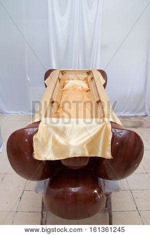 Empty coffin with gold fabric prepared for funerals