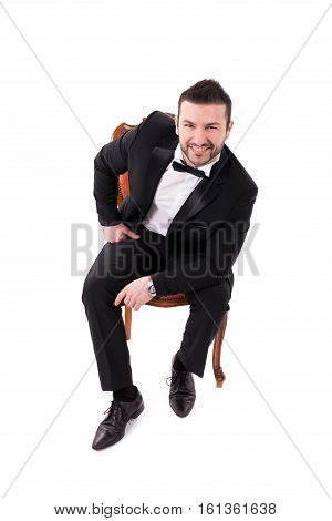 Confident Successful Smart Looking Man Smiling sitting on chair and wearing black tuxedo isolated on white background