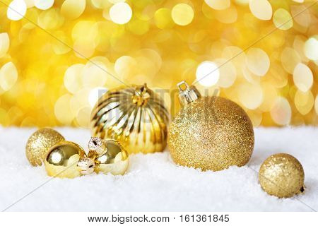 Gold Christmas balls on the shiny background. Very shallow depth of field. Selective focus