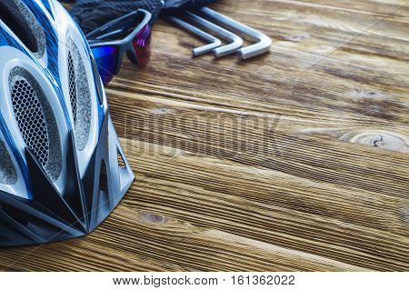 Items replacements and tools for a safe cycling: Helmet gloves glasses wrench flat lay. Top view. Tools and accessories set for cycling with copy space. Sport background.