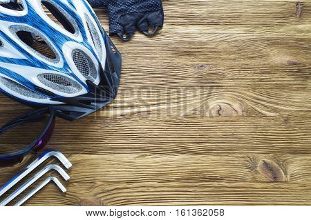 Items replacements and tools for a safe cycling: Helmet gloves glasses wrench flat lay. Top view. Tools and accessories set for cycling with copy space.