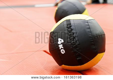 Medicine balls on red mats in the athletic gym. Exercise ball (a med ball or a fitness ball) - weighted ball roughly the diameter of the shoulders. Shallow focus.