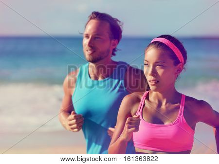 Couple athletes runners running on beach. Interracial young adults asian woman, caucasian man, training cardio together doing outdoor workout jogging. Photo filtered, pink color filter.
