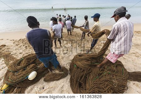 GALLE SRI LANKA - DECEMBER 09 2016 : Fishermen stood and work in the a boat on the beach at Galle city on December 12 2016 Fishermen on beach in the morning for sald many fish at Galle Sri lanka.