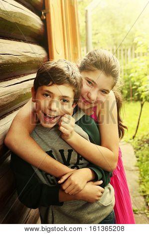siblings boy girl teenager hug smile on the country garden garden